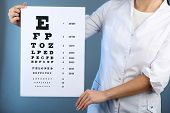 Health care, medicine and vision concept - woman with eye chart on color background