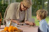 stock photo of grandma  - Grandson and his grandma dishing up homemade cake - JPG
