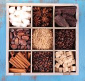 Wooden box with set of coffee and cocoa beans, sugar cubes, dark chocolate, cinnamon and anise on wooden background