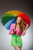 Woman holding colourful umbrella in studio