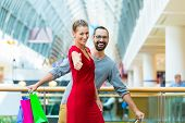 Couple, man and woman, in modern shopping mall with bag