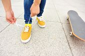 young woman skateboarder tying shoelace