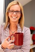 Happy blonde woman holding tea mug in hand, smiling, looking at camera.