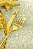 Christmas golden cutlery and ornaments on festive background
