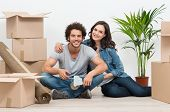 Happy Young Couple Surrounded With Cardboard Boxes At Home