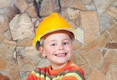 Young funny constructor with a stone wall of background