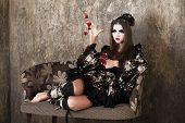 Beautiful young woman in black kimono dress on gray background
