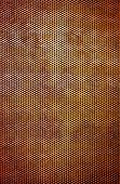 Industrial background of a rusty iron surface perforated with many holes