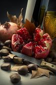 Autumn Fall still-life with red wine, pomegranate and chestnuts