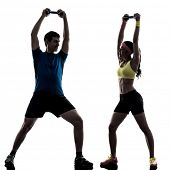 one woman exercising fitness weight training with man coach in silhouette on white background