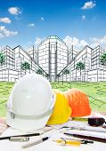 stock photo of land development  - architect working table with writiing tool safety helmet and perspective plan drawing of new building construction project for land development and real estate design - JPG