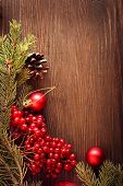 Christmas tree ornaments and viburnum berries on wooden background space for lettering