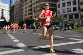 VALENCIA, SPAIN - NOVEMBER 16, 2014: Woman runner Bea Molina of Spain competes in the 2014 Valencia Marathon.  Molina was the first Spanish woman to cross the finish line with a time of 2:52:38.