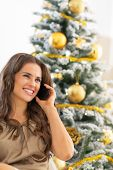 Portrait Of Happy Young Woman Talking Cell Phone Near Christmas Tree