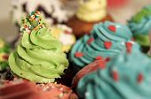 Muffins With Colorful Cream And Sprinkles