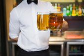 Bartender holding two glasses of beer in a bar