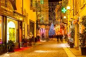 ALBA, ITALY - DECEMBER 30, 2013: Pedestrian street and shops in old town illuminated for Christmas and New Year holidays. This area is very popular with locals and tourists visiting Alba for holidays.