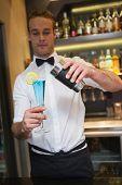 Handsome bartender serving blue cocktail in a bar