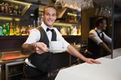 Smiling waiter offering cup of coffee smiling at camera in a bar
