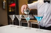 Bartender pouring blue alcohol into cocktail glass in a bar