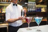 Attractive bar man making a cocktail in a bar