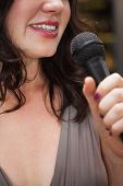 Close up of beautiful woman singing into a microphone at the nightclub