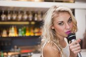 Pretty blonde woman singing while looking at camera at the nightclub