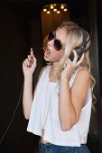 Pretty blonde in sunglasses listening to music and singing at the nightclub