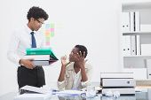 Man giving pile of files to his irritated colleague in the office