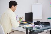 Designer using digitizer and colour sample in his office