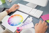 Designer using computer and colour wheel in his office