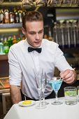 Bartender preparing a drink at bar counter in a bar