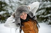portrait of beautiful smiling female in luxurious fur head cloth outdoor in winter