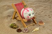deck chair with euro currency on the sandy beach. symbol photo for costs in travel, vacation, holidays. save on vacation