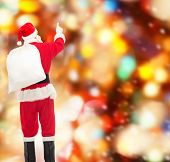 christmas, holidays and people concept - man in costume of santa claus with bag pointing finger from back over red lights background