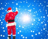 christmas, holidays and people concept - man in costume of santa claus writing something from back over blue snowy background