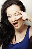 Closeup portrait of charming young woman peeking though her fingers
