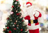 christmas, holidays and people concept - man in costume of santa claus with bag and christmas tree waving hand over lights background