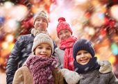 family, childhood, season, holidays and people concept - happy family in winter clothes over red lights and snow background