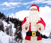 christmas, holidays, food, drink and people concept - man in costume of santa claus with glass of milk and cookies over snowy mountains