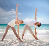 fitness, sport, friendship and lifestyle concept - couple making yoga exercises on summer beach