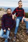 Couple of stylish hipster guys sitting on rock cliff, hiker man and woman sitting on mountain hill