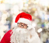 christmas, holidays and people concept - close up of santa claus in glasses winking over lights background