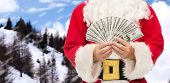 christmas, holidays, winning, currency and people concept - close up of santa claus with dollar money over snowy mountains