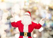 christmas, holidays and people concept - man in costume of santa claus with raised hands over lights background