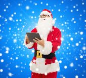 christmas, holidays, technology and people concept - man in costume of santa claus with tablet pc computer over blue snowy background