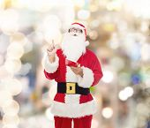 christmas, holidays, gesture and people concept - man in costume of santa claus with notepad pointing finger up over lights background
