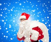 christmas, holidays and people concept - man in costume of santa claus with bag making hush gesture over blue snowy background