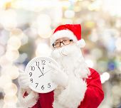 christmas, holidays and people concept - man in costume of santa claus with clock showing twelve over lights background