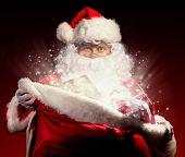 Santa Claus in costume holding wish list. Dark pattern as background